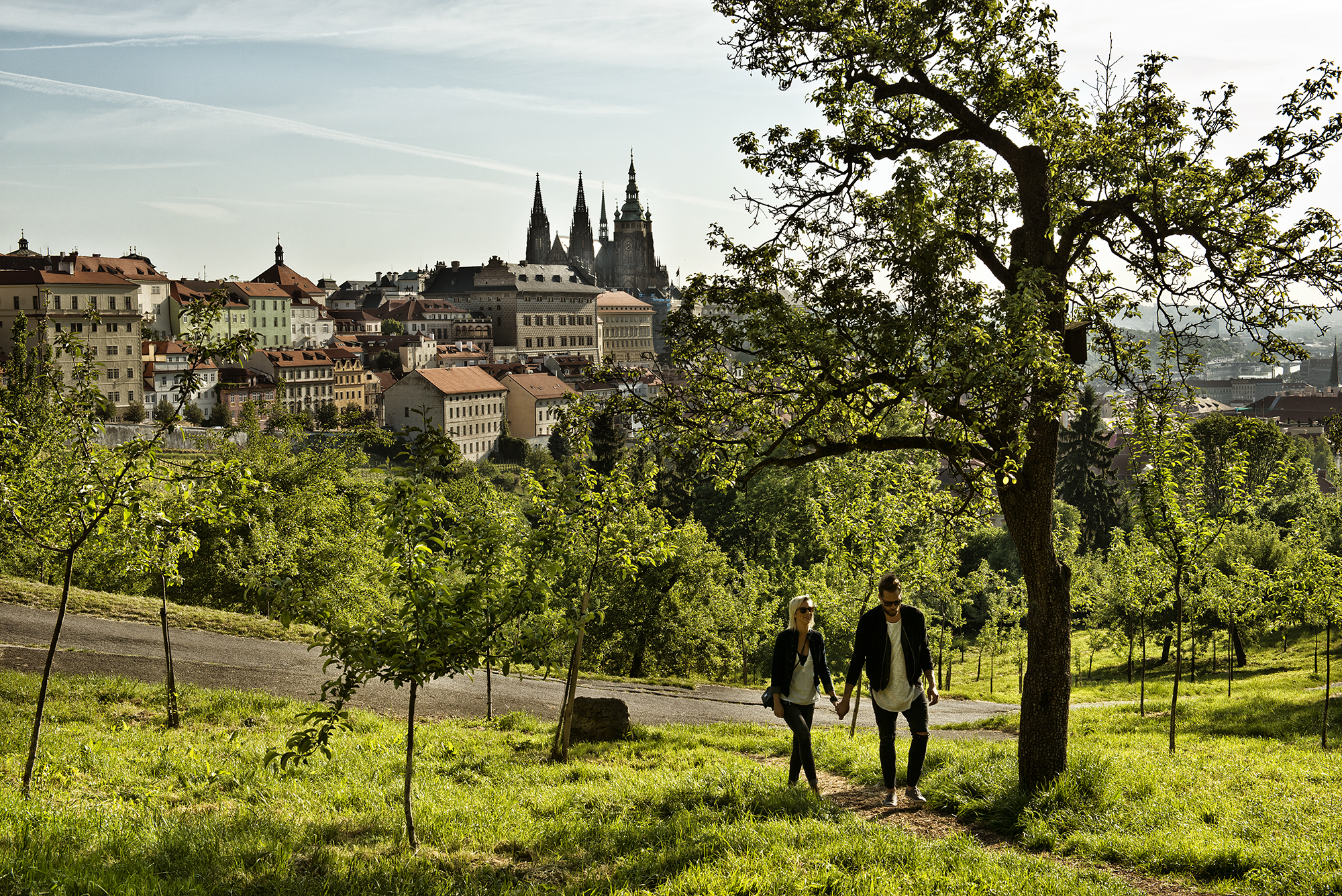 A spring view of the Prague Castle panorama in the background, with a young couple walking up the Petřín Hill path in the foreground